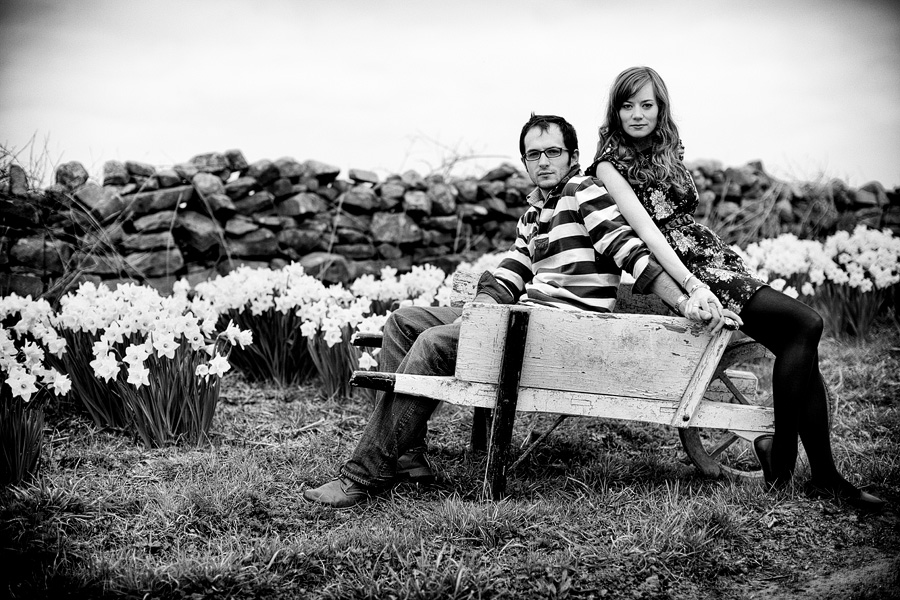 Couple hold hands seated on a wooden wheelbarrow. Black and white image from Yorkshire engagement shoot