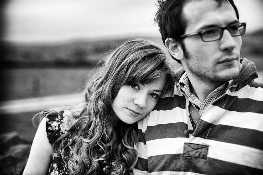 Monochrome pre-wedding shoot photograph - girl looks at camera leaning on the shoulder of her partner who looks away to the right