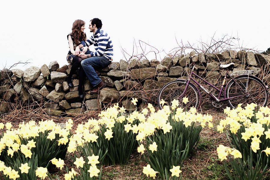 Couple sit on rustic stone wall laughing on left of frame. To the right a bicycle leans against the wall and in the foreground are daffodils. Engagement shoot image