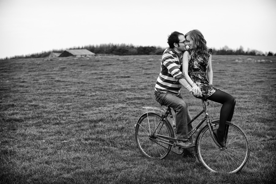 man sits on bike in field with his fianceé sitting on handlebars, their heads together. Sweet documentary style engagement shoot image