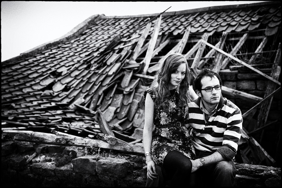 Black & white engagement photograph - couple sit in front of ruined out-building