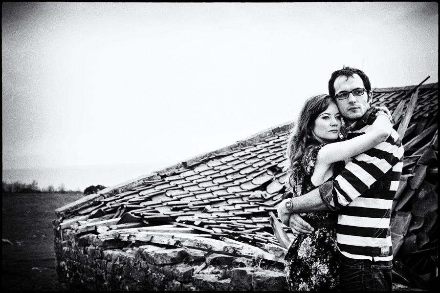 Couple stand in front of ruined out-building - monochrome rustic engagement shoot photograph