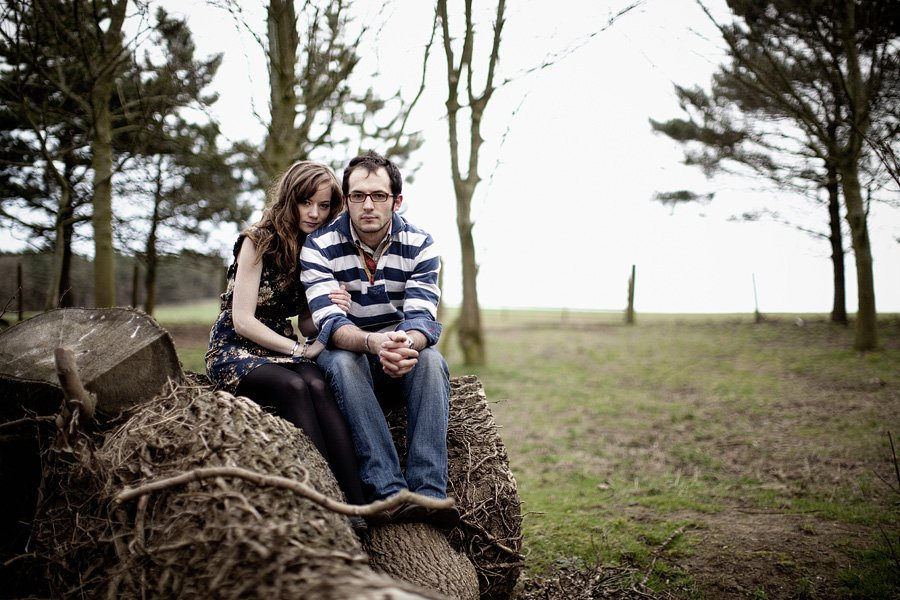 Couple sit on tree stump looking at camera in rustic engagement shoot photograph