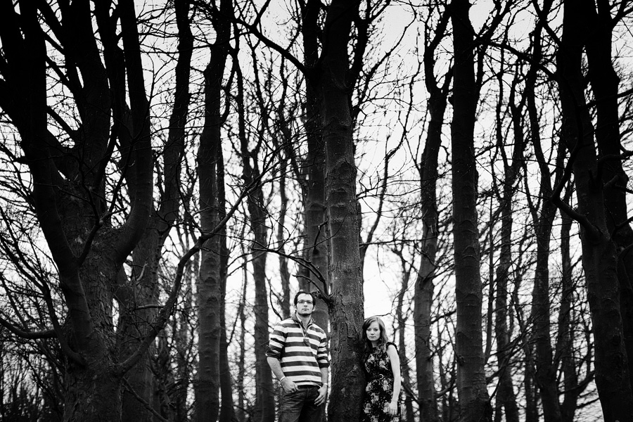 Couple stand in forest looking towards camera, engagement photograph taken at distance in black & white
