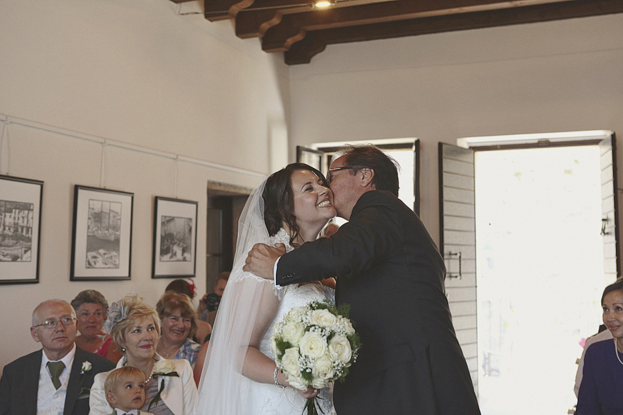 The bride kissing her father at the ceremony