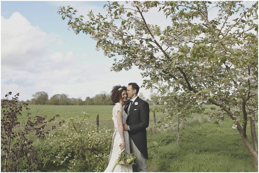bride and groom under blossom tree