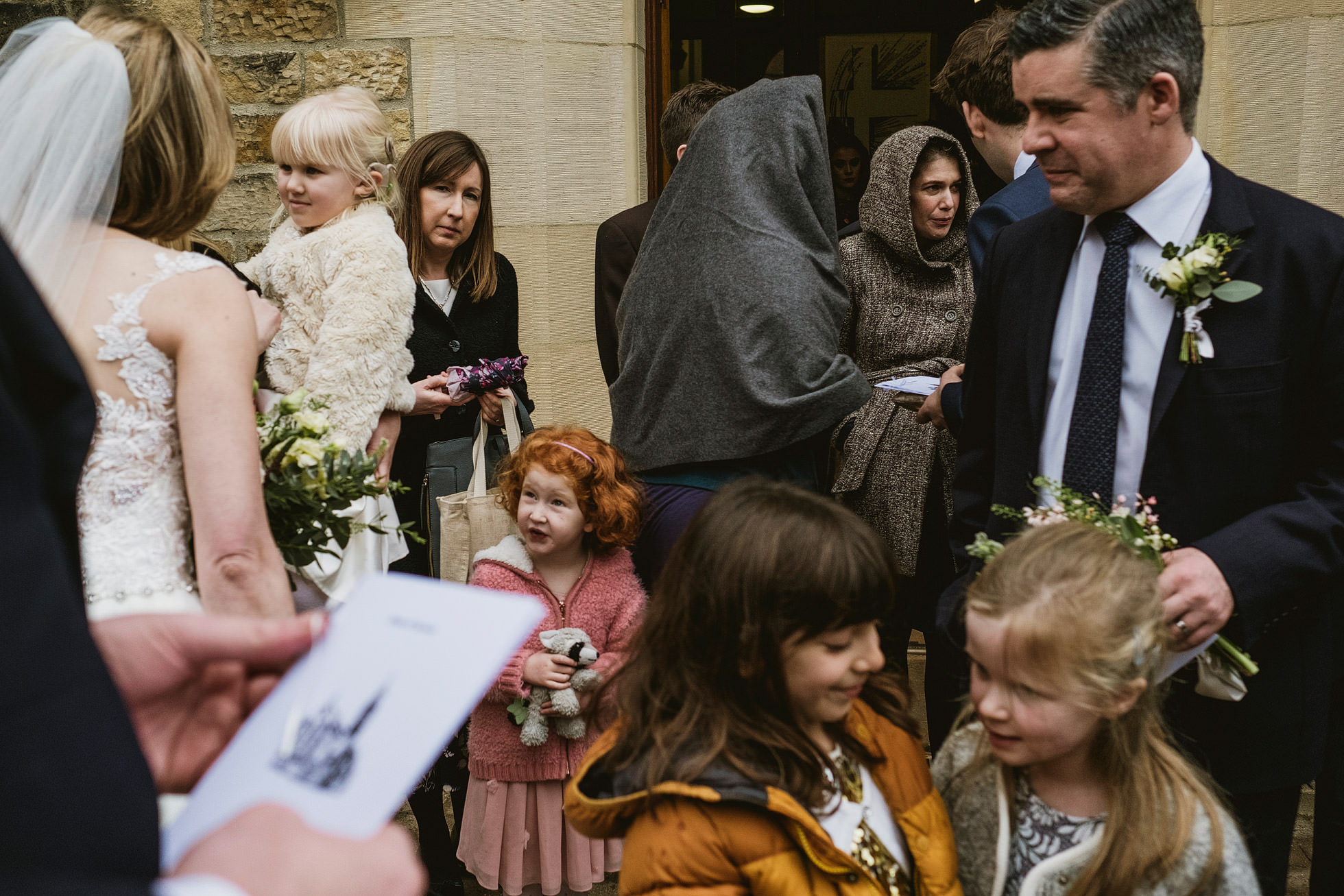 Group of wedding guests and children gather at Lartington Hall before wedding ceremony - layered documentary wedding photography