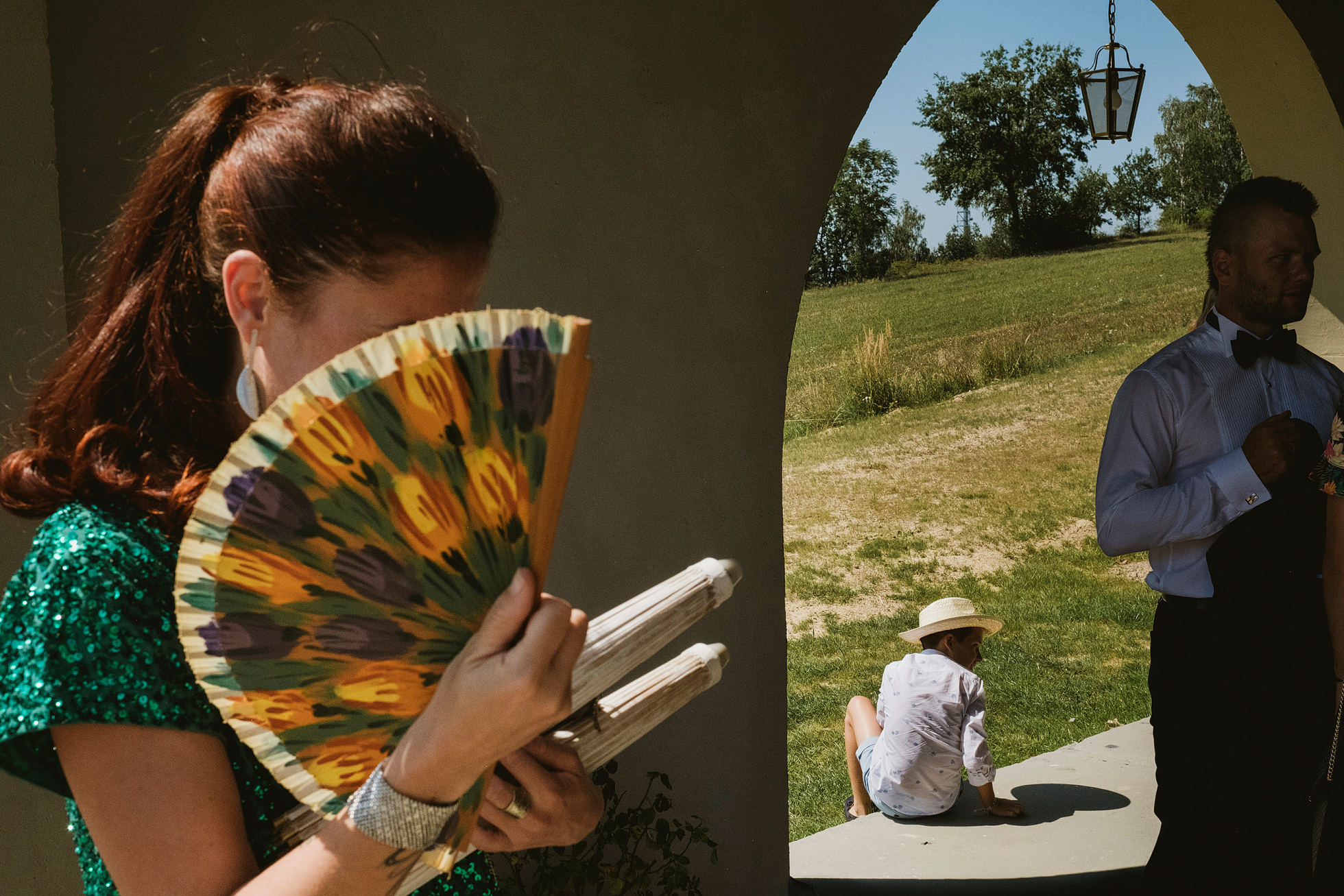 woman with fan, child framed in doorway and groosman preparing for wedding in Krakow