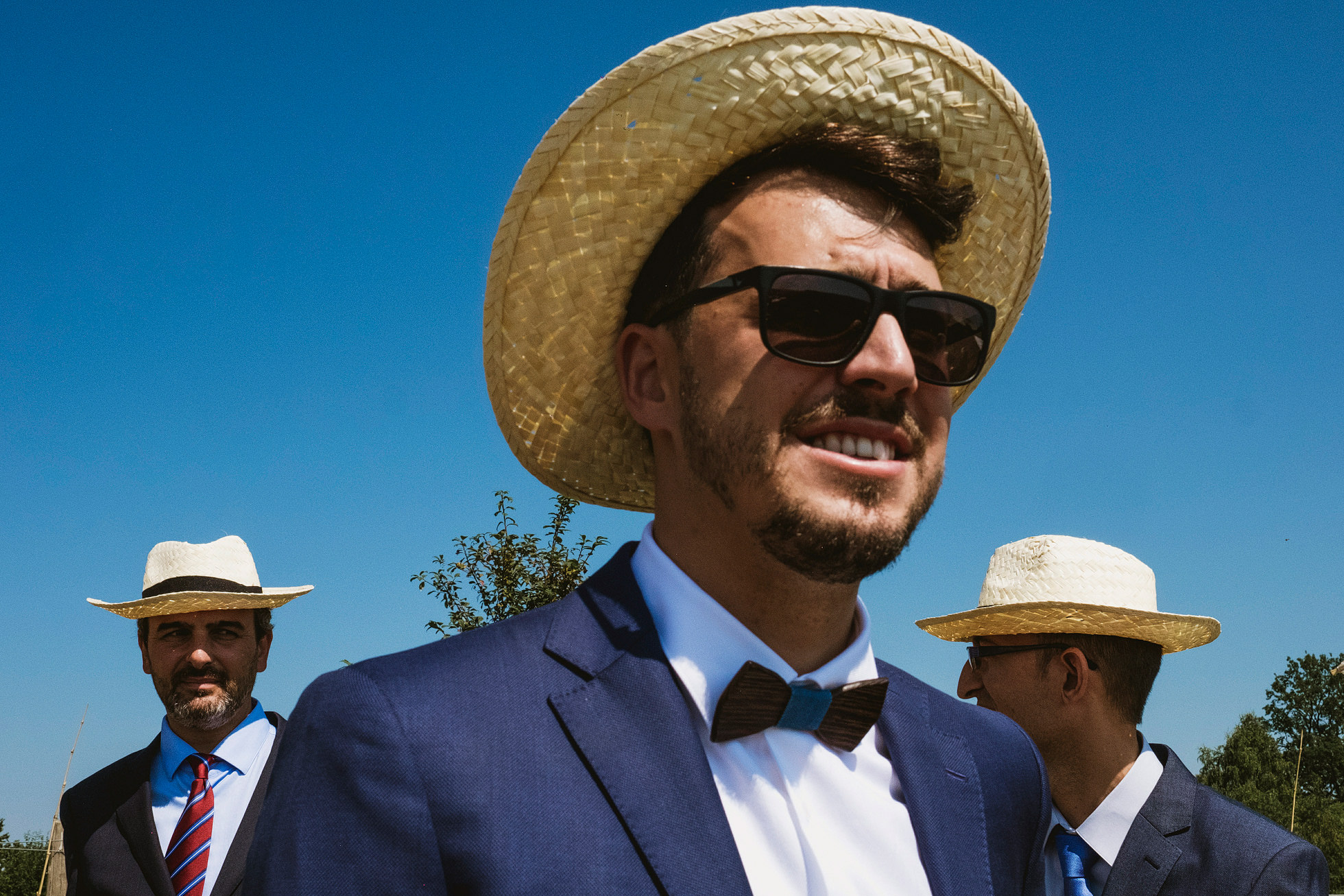Three men in straw hats at Polish wedding