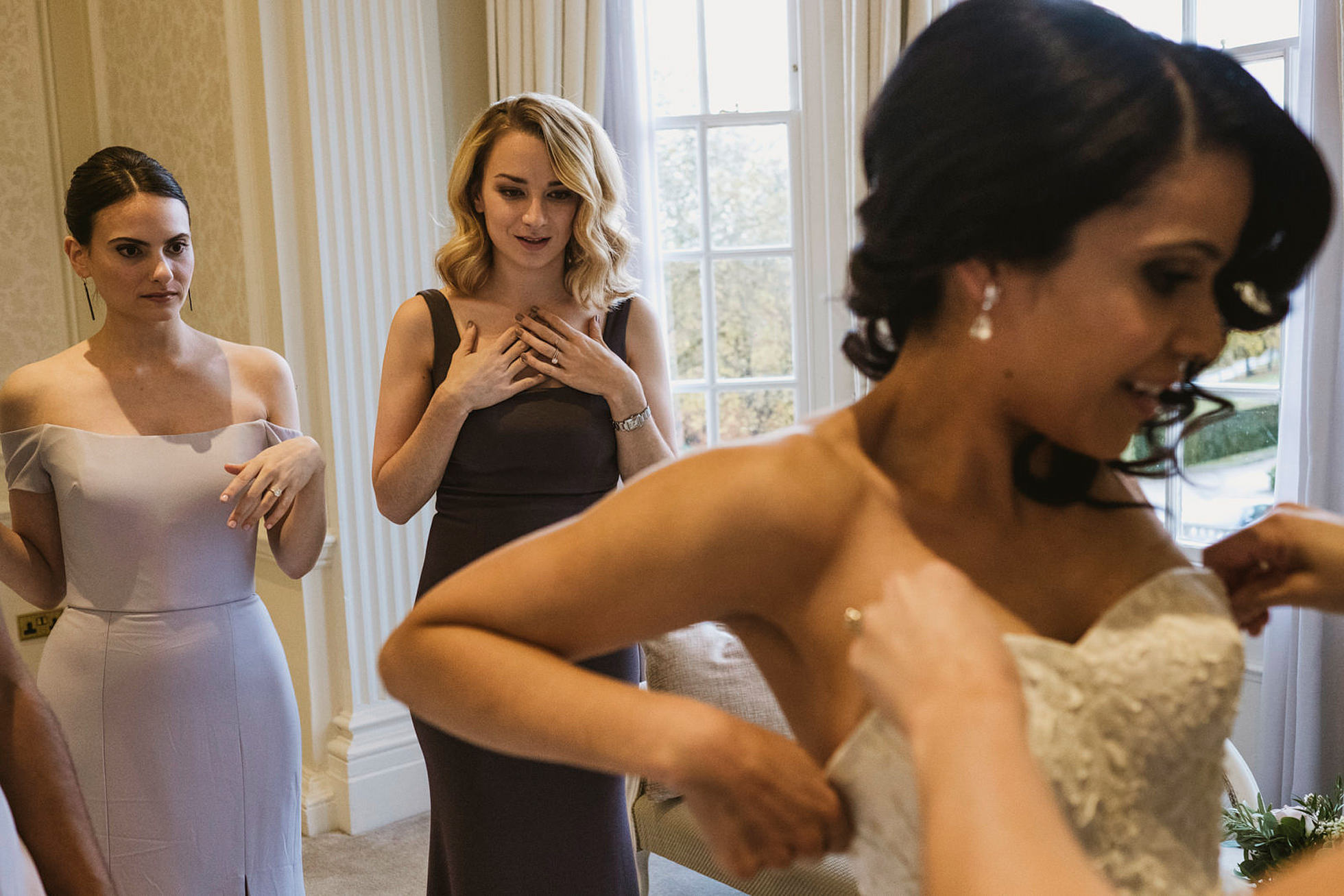 Bride being helped into wedding dress, Hedsor House